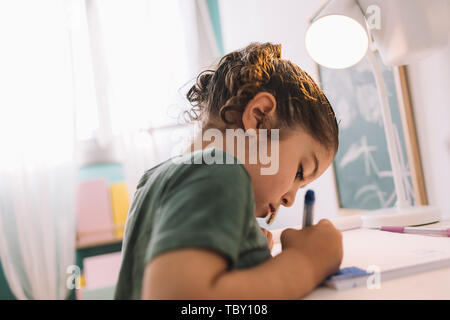 little girl draws concentrated at home with color markers, she is drawing on the desk in her room - Stock Photo
