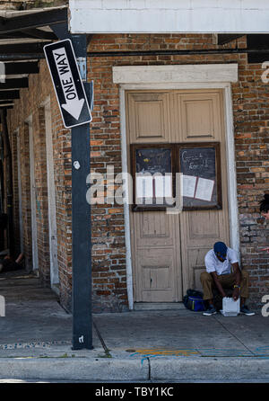 New Orleans, LA, USA -- May 23, 2019.  A Man sits in the doorway of an old Saloon;  a broken One Way sign points down. - Stock Photo