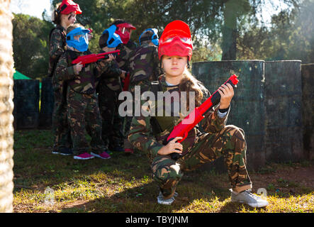 sportive girl paintball player in camouflage standing with gun before playing outdoors - Stock Photo