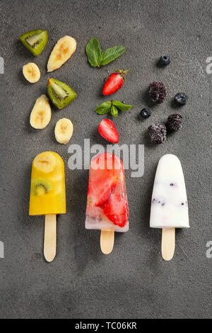 Different fruit ice cream on grey background - Stock Photo