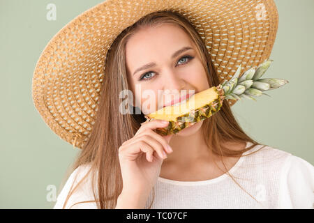 Beautiful young woman eating pineapple on color background - Stock Photo