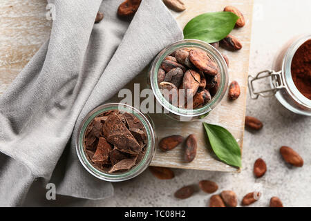 Jars with cocoa beans and chocolate on light background