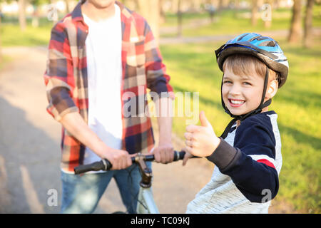 Father teaching his son to ride bicycle outdoors - Stock Photo