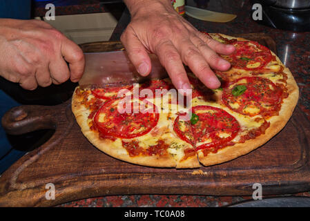 Pizza. Fresh Italian neapolitan, basil and tomato on a wooden table - Stock Photo
