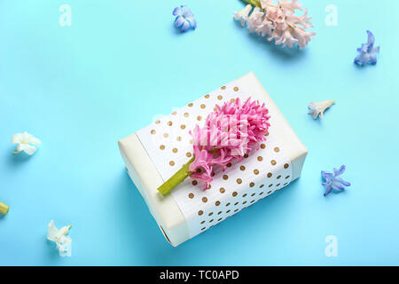 Beautiful gift box and flowers on color background - Stock Photo