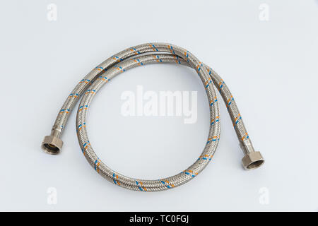 Flexible tube for water in a metal braid on a white background - Stock Photo