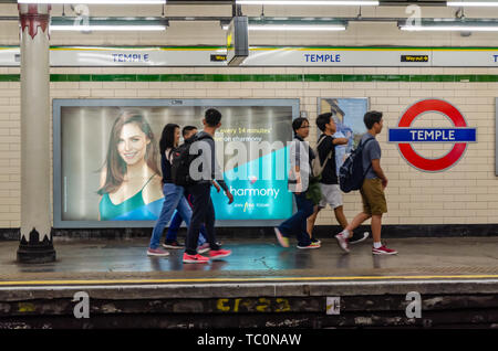 A group of young adults walk along the platform at Temple London Underground station. - Stock Photo