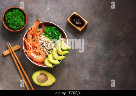 Bowl poke shrimp, rice, avocado, chuka, soy sauce and sesame on a dark rustic background. Top view, flat lay, copy space - Stock Photo