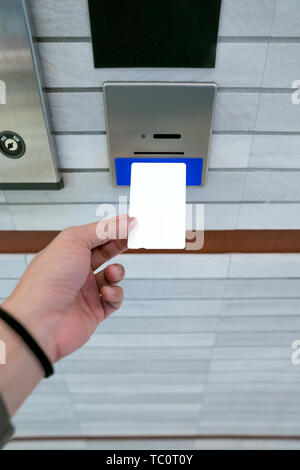 securing lift or elevator access control, man's hand is holding a key card lay up to insert in card hold for unlocking elevator doors before up or dow - Stock Photo
