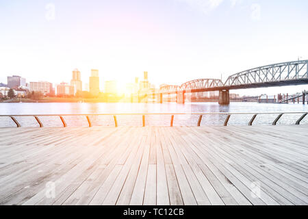 empty wood floor near steel bridge with cityscape and skyline of portland at sunrise - Stock Photo