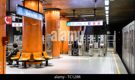 Passengers waiting for a train or leaving the Gare du Midi/Zuidstation subway station, located under the Brussels-South railway station in Belgium. - Stock Photo