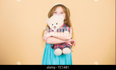 Her favorite toy. Little girl holding soft toy. Small child cuddling teddy bear toy. Adorable girl child with cute stuffed animal doll. Toy is used in play. - Stock Photo