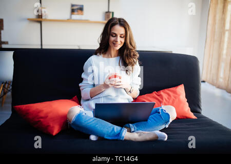 Smiling beautiful brunette relaxing on the couch and using her laptop in the living room - Stock Photo