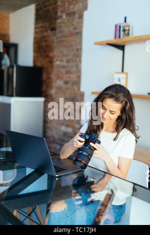 Young freelance female photographer at home, working on laptop in home office - Stock Photo