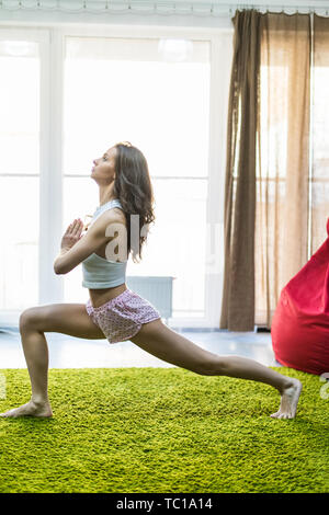 Young woman practicing yoga exercises at home interior in the morning - Stock Photo