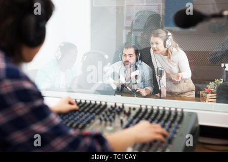 Positive presenters and guests in sound broadcasting station hosting live radio show. View from room where audio engineer controlling sound on air - Stock Photo