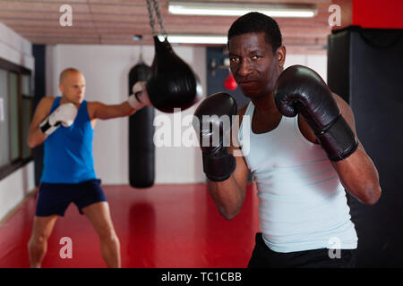 Potrait of smiling cheerful positive african american boxer who is training in gym - Stock Photo