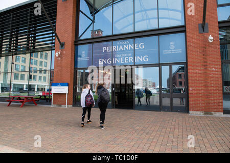 Higher education in the UK: Two women students entering the College of Engineering building on Swansea University Bay Campus, South Wales, UK - Stock Photo
