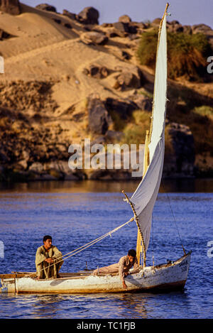 Luxor, Egypt. Two boys sail their small felucca sail boat on the river Nile. Photo: © Simon Grosset. Archive: Image digitised from an original transpa - Stock Photo