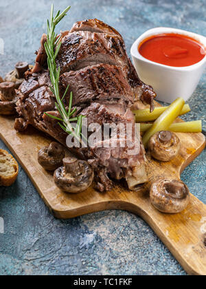 Close-up grilled ram leg with mushrooms, vegetables, spices on a cutting board. Halal meat and food - Stock Photo