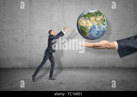 Side view of little businessman reaching out for planet Earth that is levitated above big man's hand emerging from right. - Stock Photo