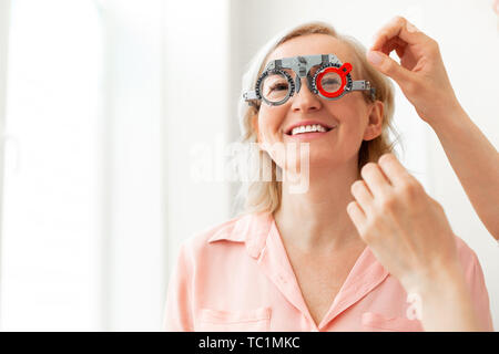 Size of lens. Short-haired patient with wide smile trying on different lenses while having appointment with ophthalmologist - Stock Photo