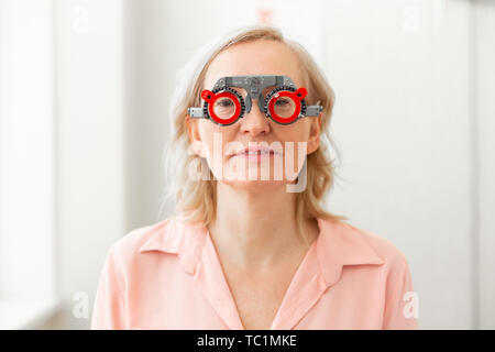 Control trying on. Calm senior patient in pink shirt having special construction on while trying on different lenses - Stock Photo