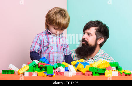 father and son play game. happy family. leisure time. building home with colorful constructor. child development. father and son relax. little boy with bearded dad playing together. father and son. - Stock Photo