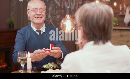 Nice old man giving his wife a beautiful ring in a red box while having dinner. Senior man smiling. - Stock Photo