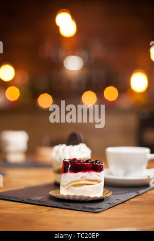 Close up of tasty mini cake with fruits on top over a wooden table in a coffee shop. Delicious cup of coffee. Cake with biscuit on top. - Stock Photo
