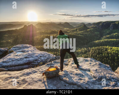 Professional photographer prepares a camera and a tripod before shooting of nature picture on the mountain summit. - Stock Photo