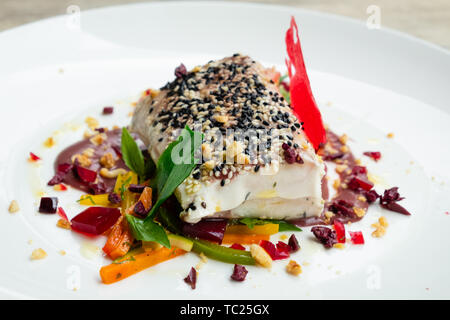 close up of slow cooked sous vide tuna loin with black and white sesame crust olive sauce, mixed vegetable wine gelatine white plate, natural light fo - Stock Photo