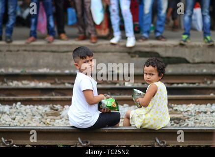 Kids seat at a train station ahead of the Muslim festival of Eid al-Fitr, in Dhaka. Muslims around the world are preparing to celebrate the Eid al-Fitr holiday, which marks the end of the fasting month of Ramadan. - Stock Photo