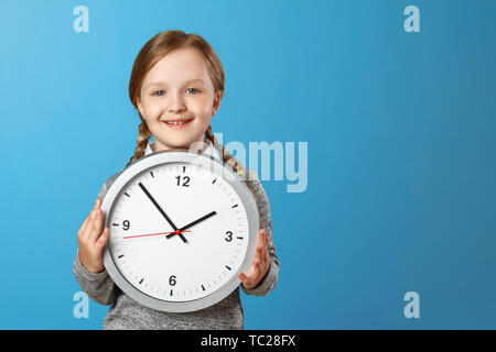 A cute little girl holding a big clock over a blue background. The concept of education, school, timing, time to learn. Copy space. - Stock Photo