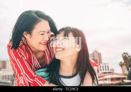 Happy mother and daughter having fun outdoor - Asian family enjoying time together outside - Concept of people lifestyle, love and parenthood