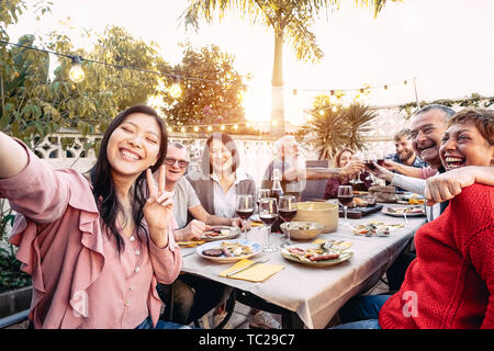 Happy family cheering and toasting with red wine glasses at dinner outdoor - People with different ages and ethnicity having fun at bbq party - Stock Photo