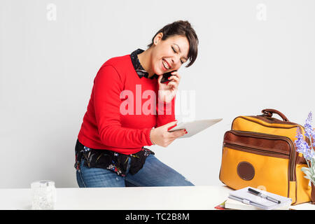 Front view of beautiful woman with ponytail sitting on a stool while using phone and holding a tablet pc against white background - Stock Photo