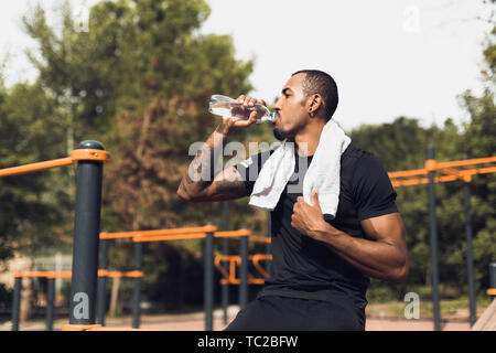 Sporty Man Drinking Water After Workout At Sports Ground