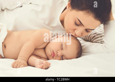 Mother kissing her sleeping newborn baby in bed - Stock Photo