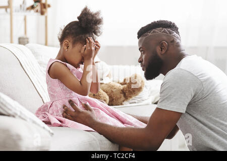 Loving african american dad comforting crying daughter - Stock Photo