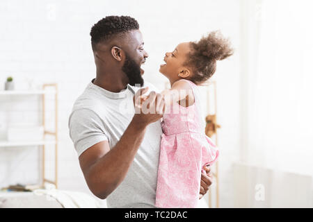 Cheerful black man dancing with his little daughter