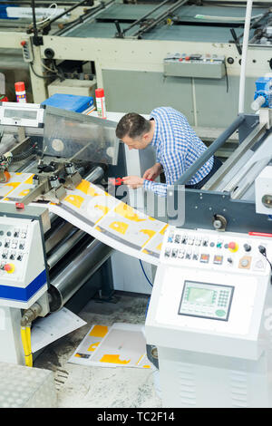 man worker near printing machine