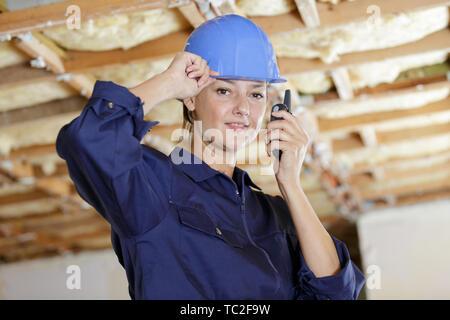 portrait of female builder using walkie talkie - Stock Photo