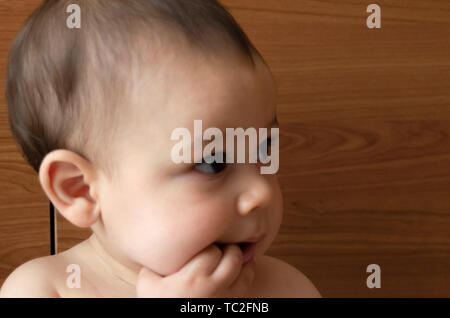 portrait face expresion of cute six months old baby boy putting finger in his mouth teething problems - Stock Photo