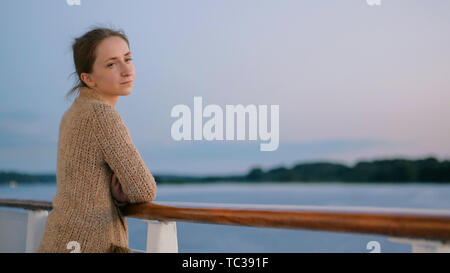 Woman admiring landscape from deck of cruise ship after sunset - Stock Photo