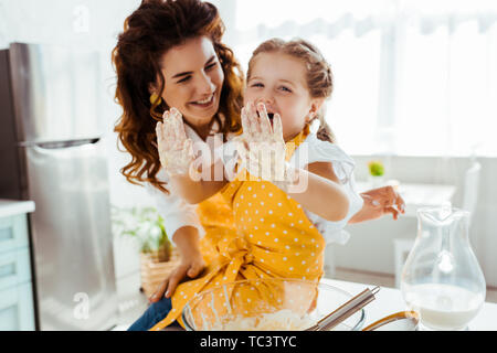 smiling mother looking at laughing daughter with dirty hands in dough - Stock Photo