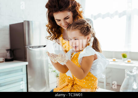 happy mother looking at laughing daughter with dirty hands in dough - Stock Photo