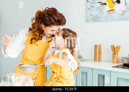 selective focus of cute mother and daughter sieving flour together in kitchen - Stock Photo