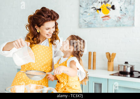 selective focus of happy mother and daughter sieving flour together in kitchen - Stock Photo