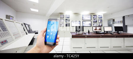 smart phone with smart home and control center in modern factory - Stock Photo
